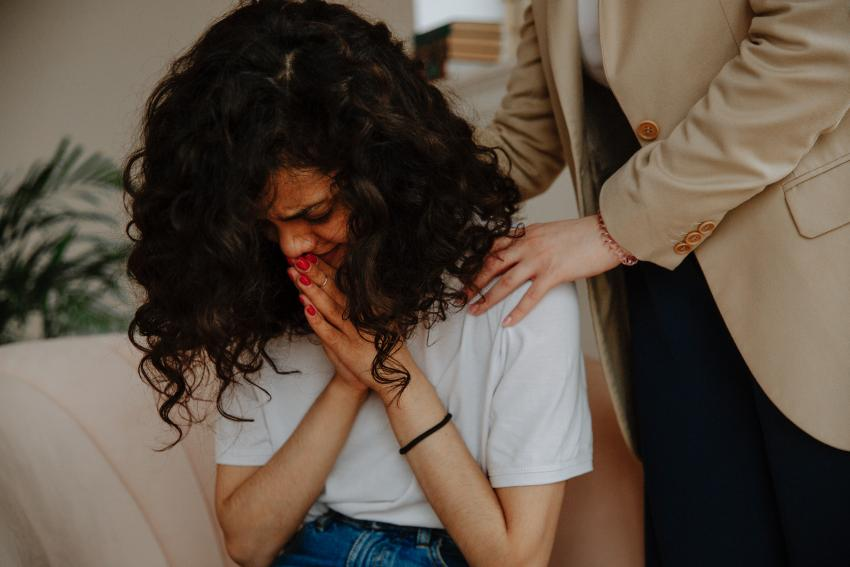 A distressed young woman is being comforted by someone whose hands are on her shoulders.