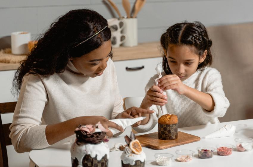 A young lady and girl decorating a cake together