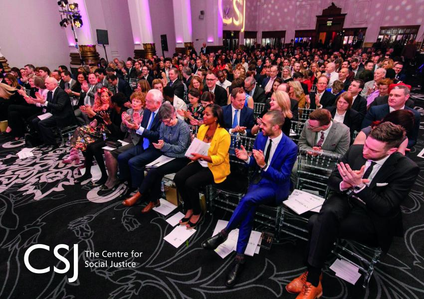 A group of people are seated clapping in a large hall. On the bottom left is the CSJ logo: the words CSJ with 'The Centre for Social Justice' written next to them in white.