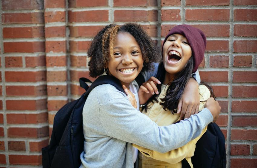 Two children embracing and laughing in front of a brick wall.