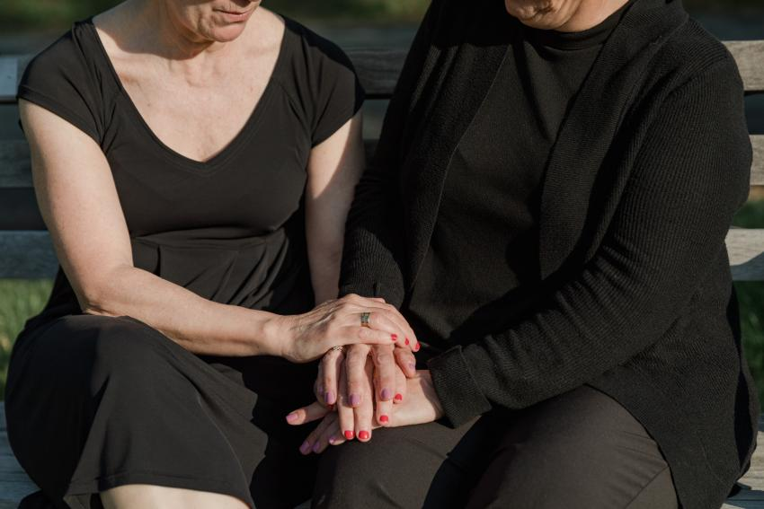 Two people dressed in black, seated on a bench, holding each other's hands.