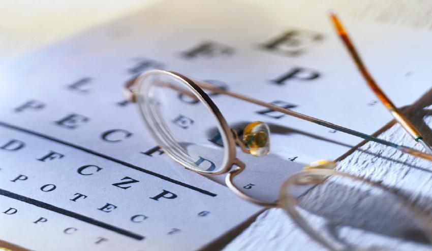 Glasses and a eye chart on a table