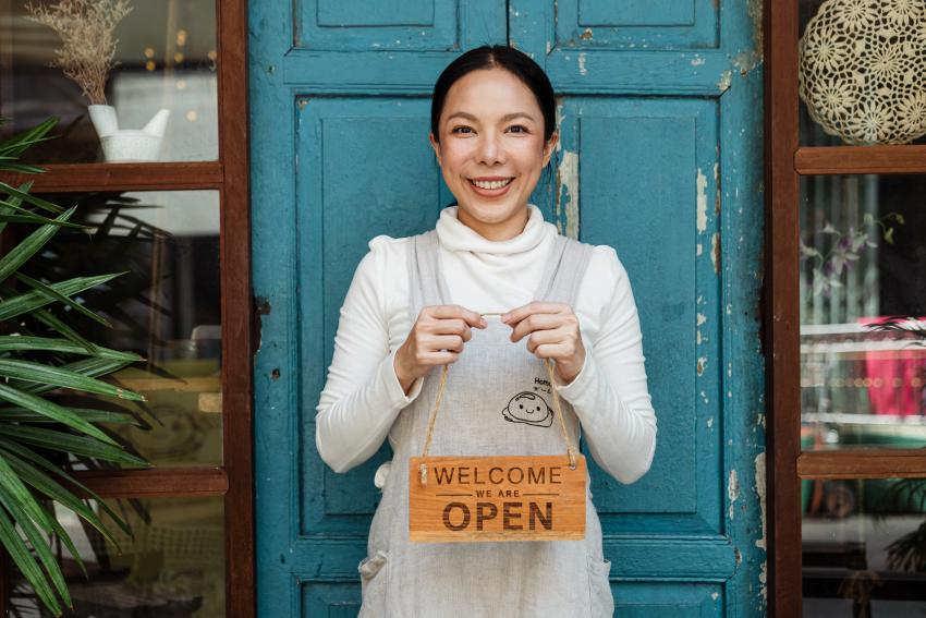 A happy shop owner standing in front of a blue door holding a sign saying 'welcome, we are open'.