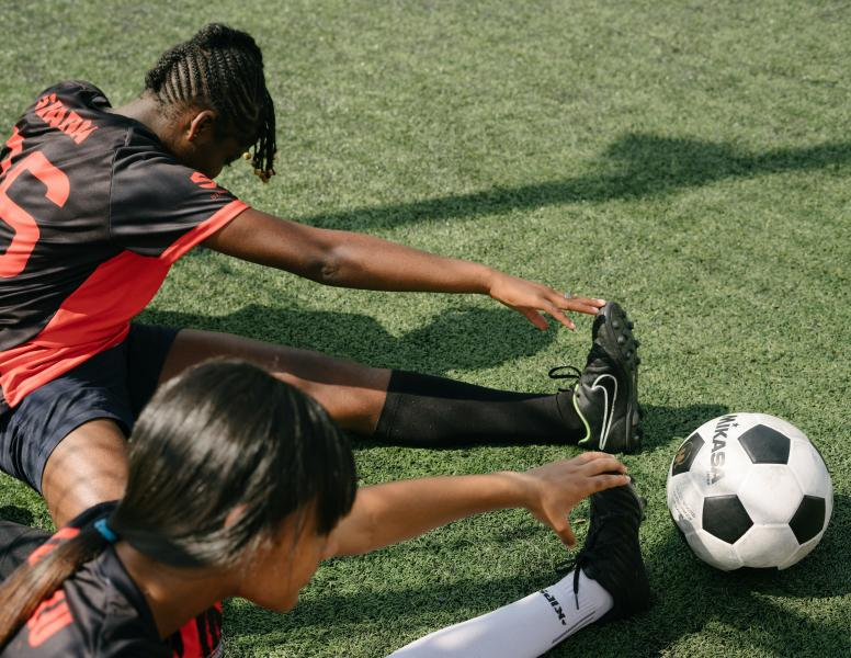 Two girls are stretching their calves next to a football.