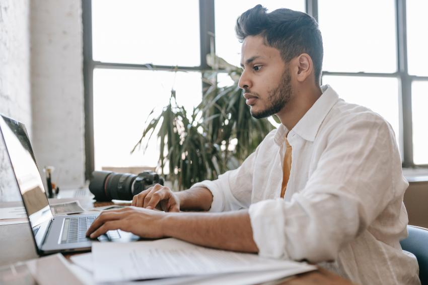 A person seated at a desk typing on their laptop.