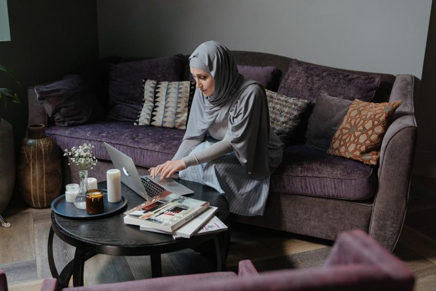 A woman is sat on a sofa looking at a laptop on a coffee table next to a pile of books.