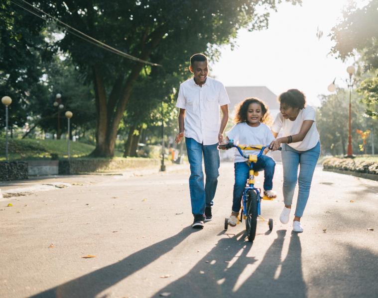 Chilld rides bike, mum helps, dad watches