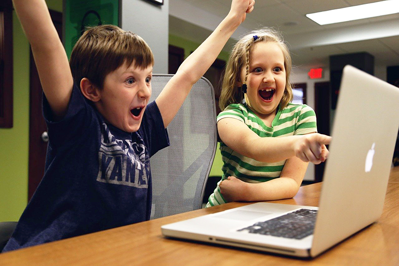 Two children celebrate success at using a laptop