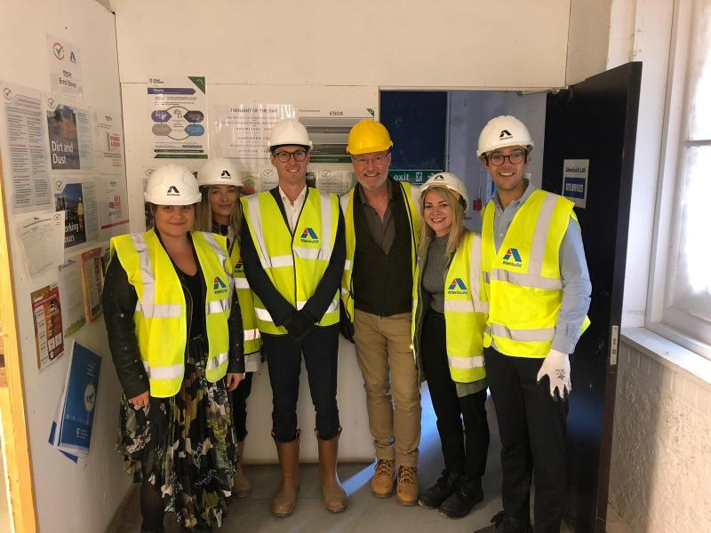Group of people posing in a building site with hard-hats on
