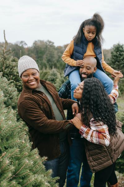 A family of four playing and laughing together at a fir tree farm.