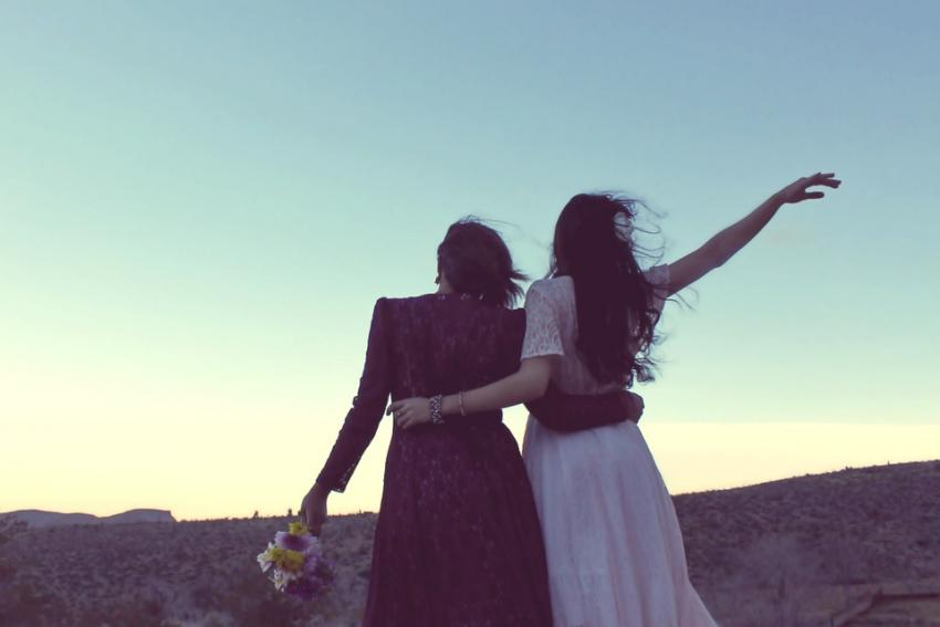 Two women embrace at sunset