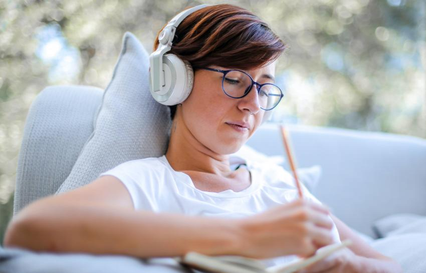 Women wearing headphone and writing down notes on some paper